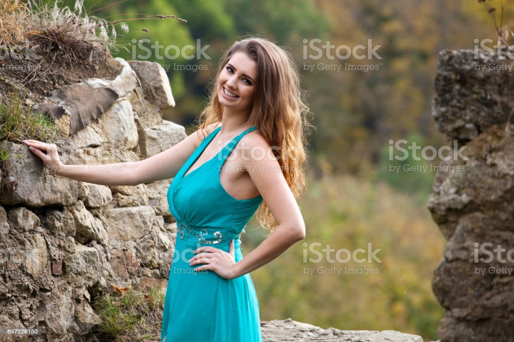 Beautiful woman near a stone wall stock photo