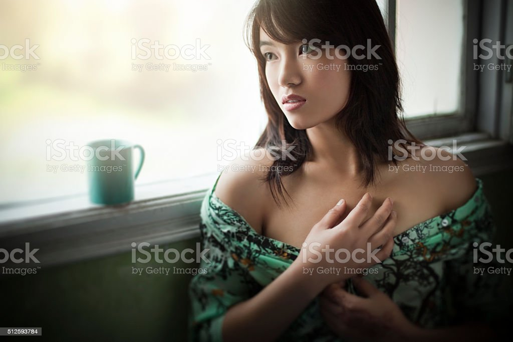 Beautiful woman near glass window at home with coffee mug. stock photo