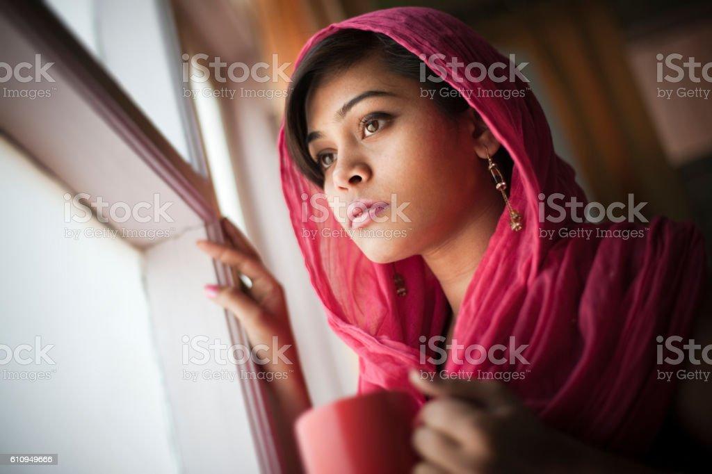 Beautiful woman near glass window at home with coffee mug. stock photo