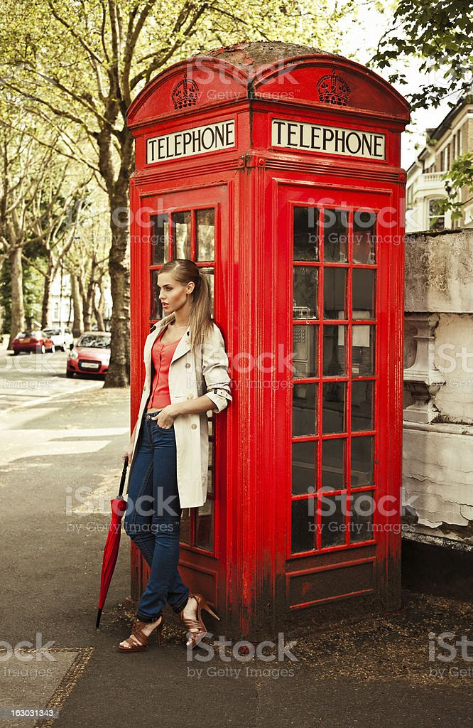 Beautiful woman next to telephone booth stock photo