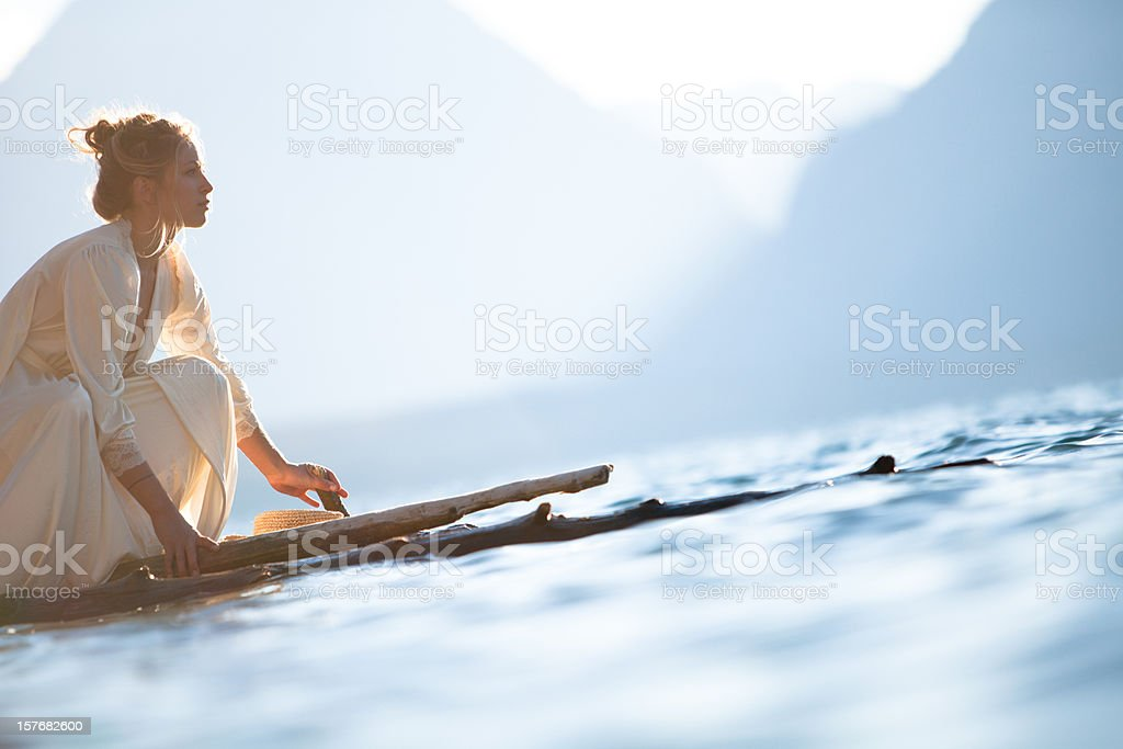Beautiful woman on a wooden raft stock photo