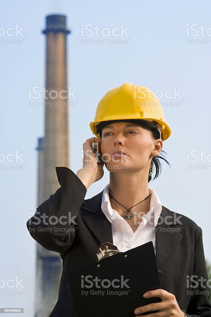 Beautiful Woman On Cell Phone Wearing Hard Hat By Chimney stock photo