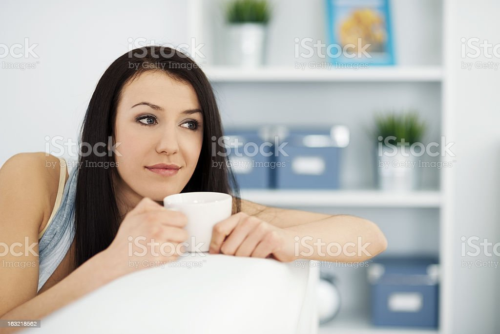 Beautiful woman on couch with cup of coffee royalty-free stock photo