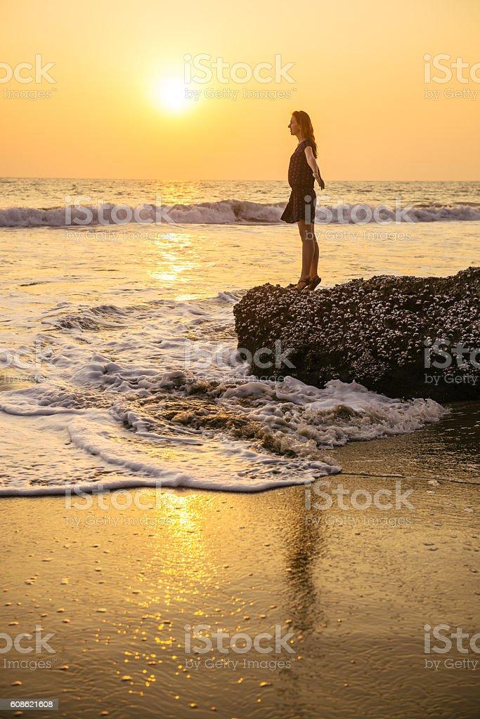 Beautiful woman on the beach at sunset stock photo