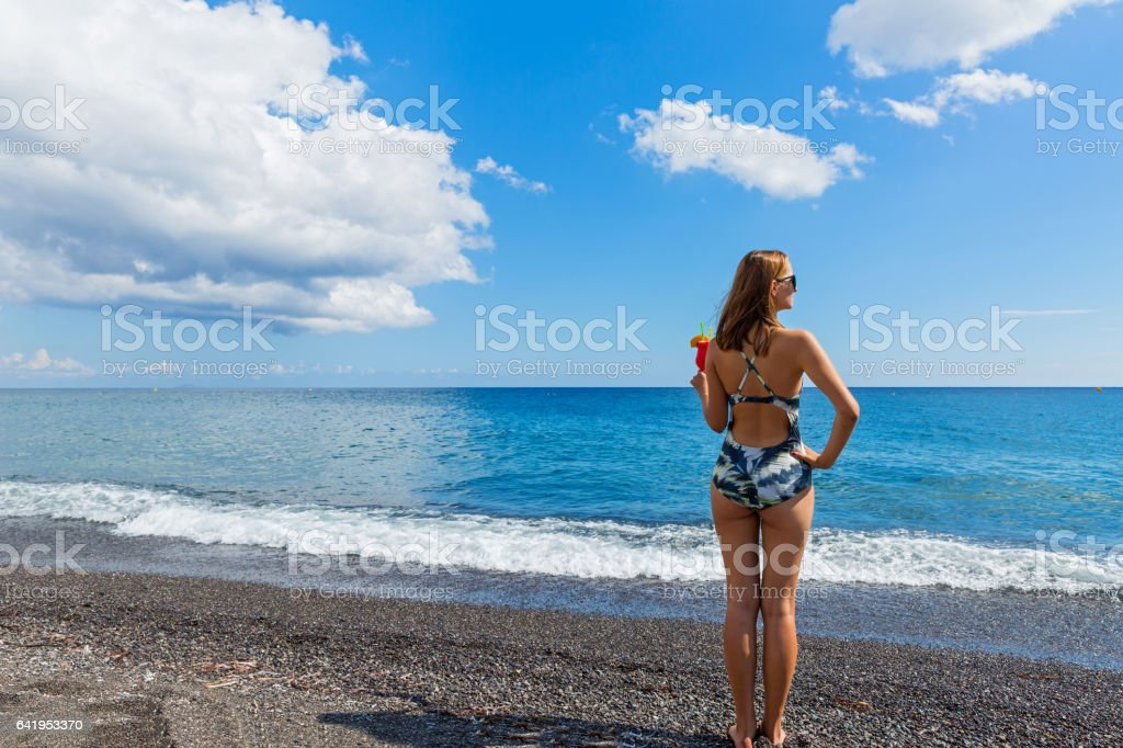 Beautiful woman on the beach with a cocktail stock photo
