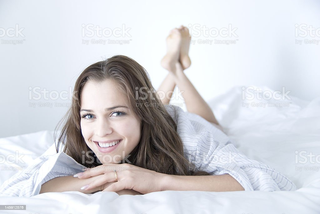 Beautiful woman on white bed royalty-free stock photo