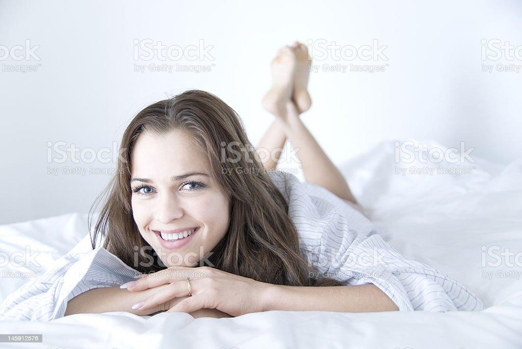 Beautiful woman on white bed stock photo