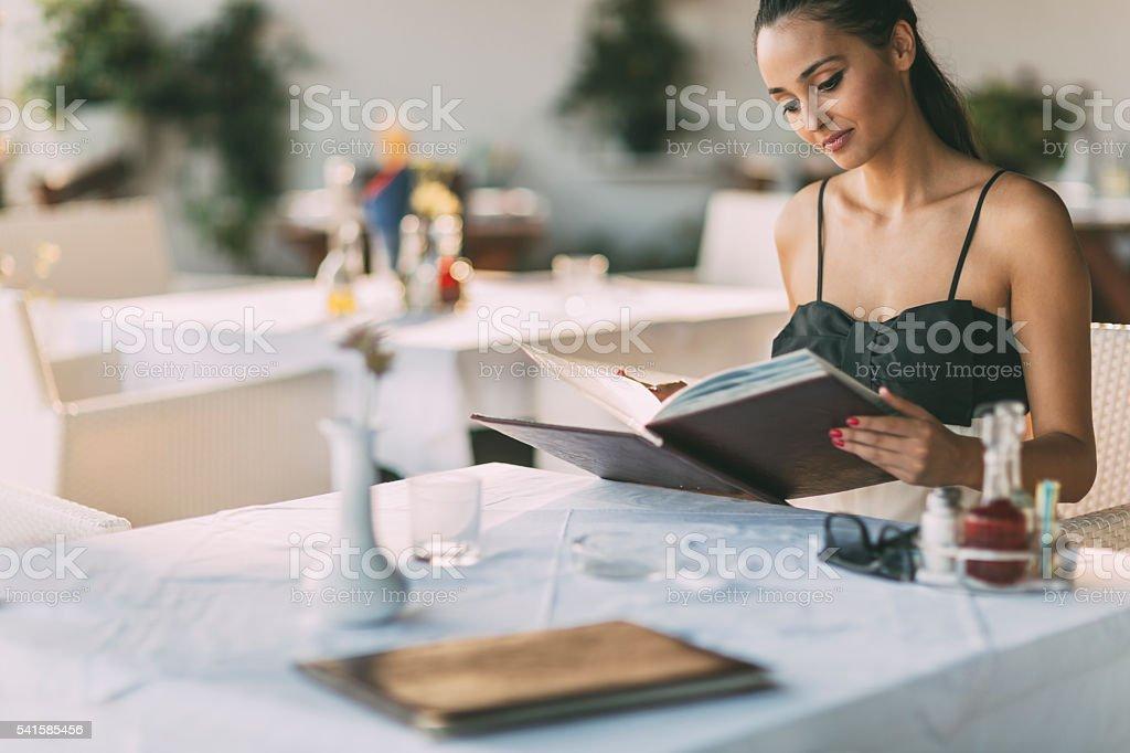 Beautiful woman ordering from menu stock photo