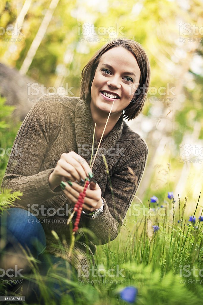 Beautiful woman outdoors holding wild strawberries royalty-free stock photo
