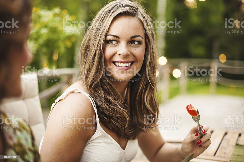 Beautiful woman outdoors on patio eating royalty-free stock photo