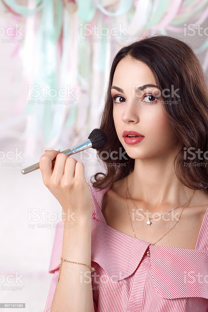 Beautiful woman painting her face with brush stock photo