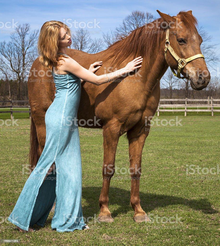 Beautiful Woman Petting Horse in Idyllic Pasture royalty-free stock photo