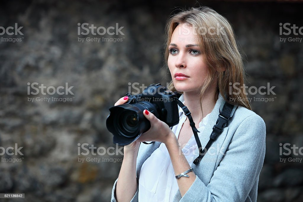 Beautiful woman photographer taking photos in the city stock photo