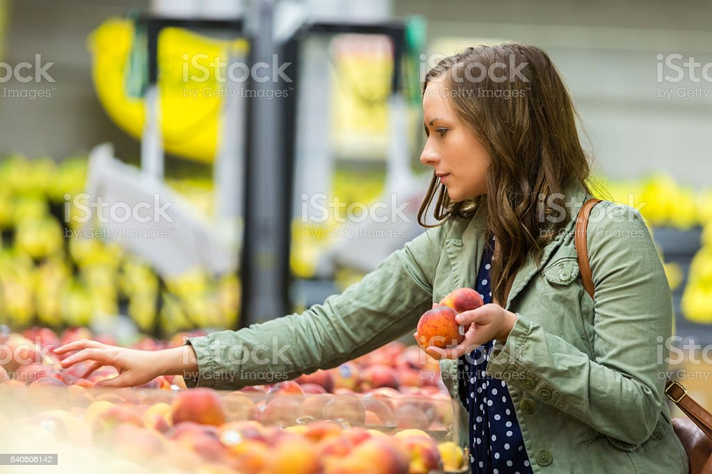 Beautiful woman picking out fruit stock photo
