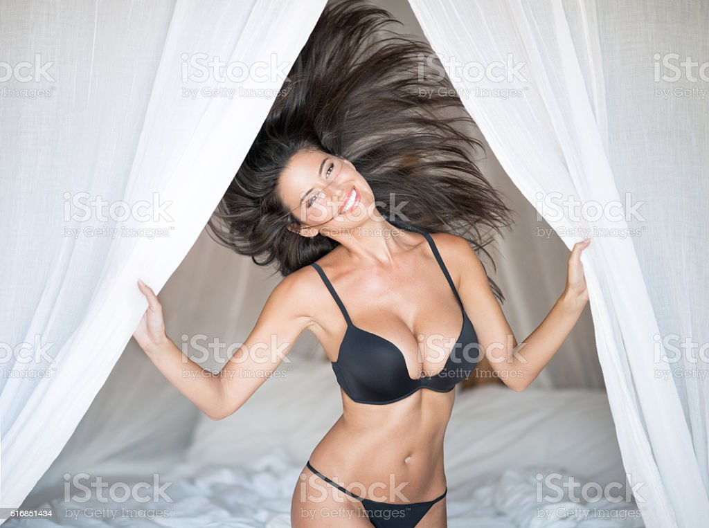Beautiful Woman playful on vacation in Bed stock photo