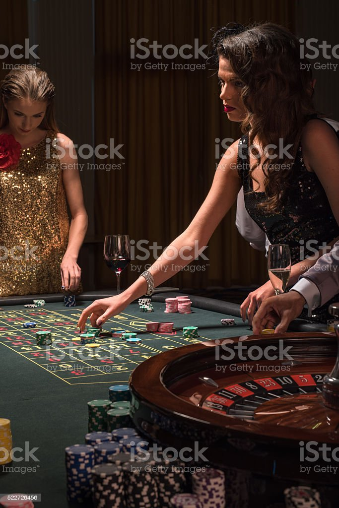 Beautiful woman playing at the roulette table stock photo