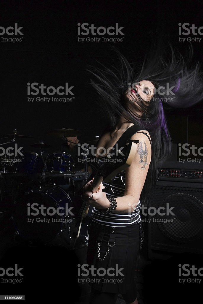 Beautiful woman playing guitar in a band with hair flying royalty-free stock photo