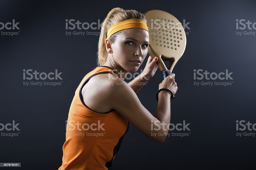 Beautiful woman playing padel indoor. Isolated on black. stock photo