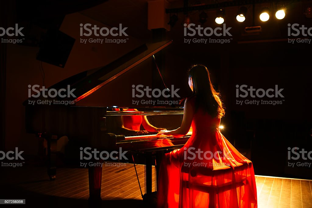 beautiful woman playing piano stock photo