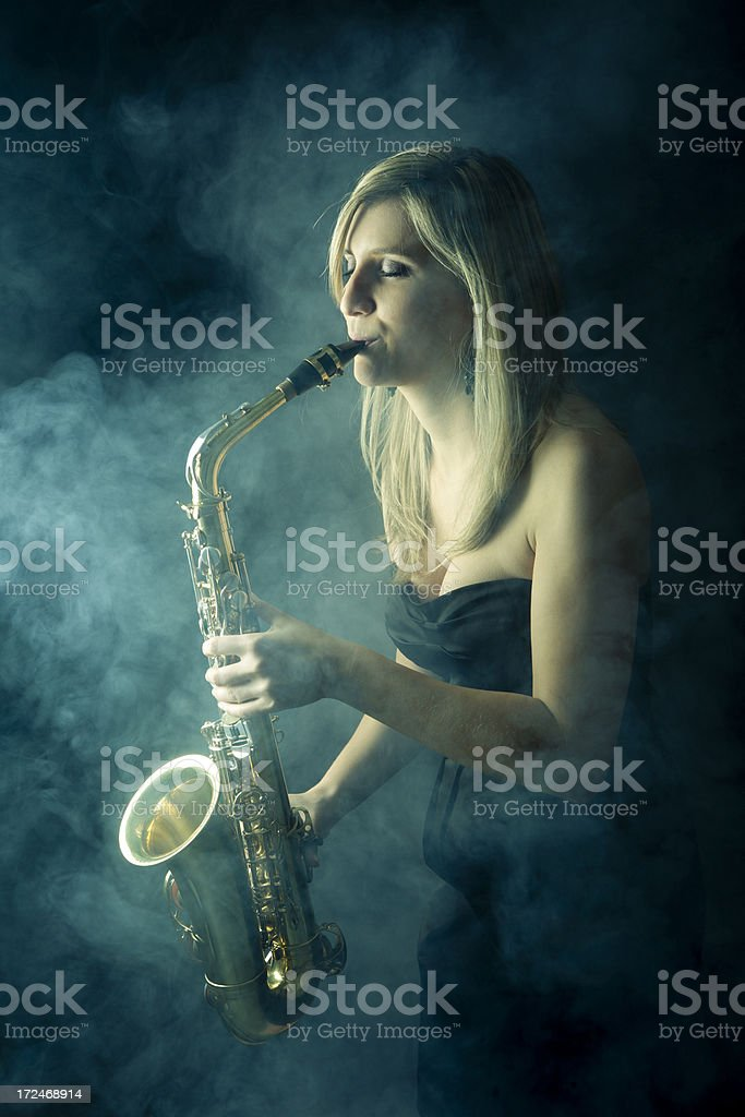 Beautiful woman playing saxophone stock photo