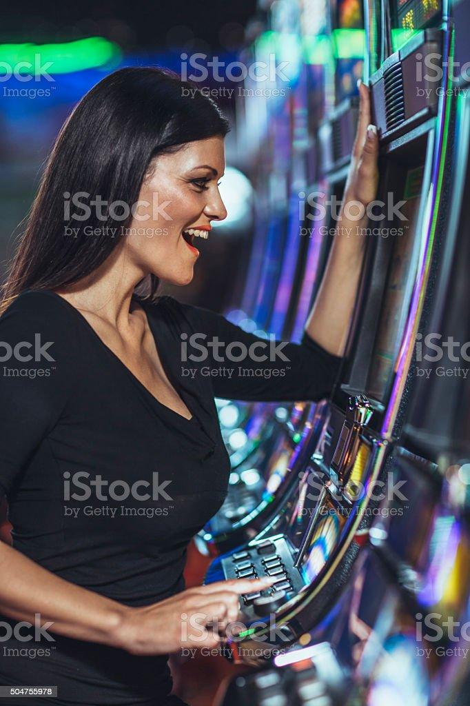 beautiful woman playing slot machine in the casino stock photo