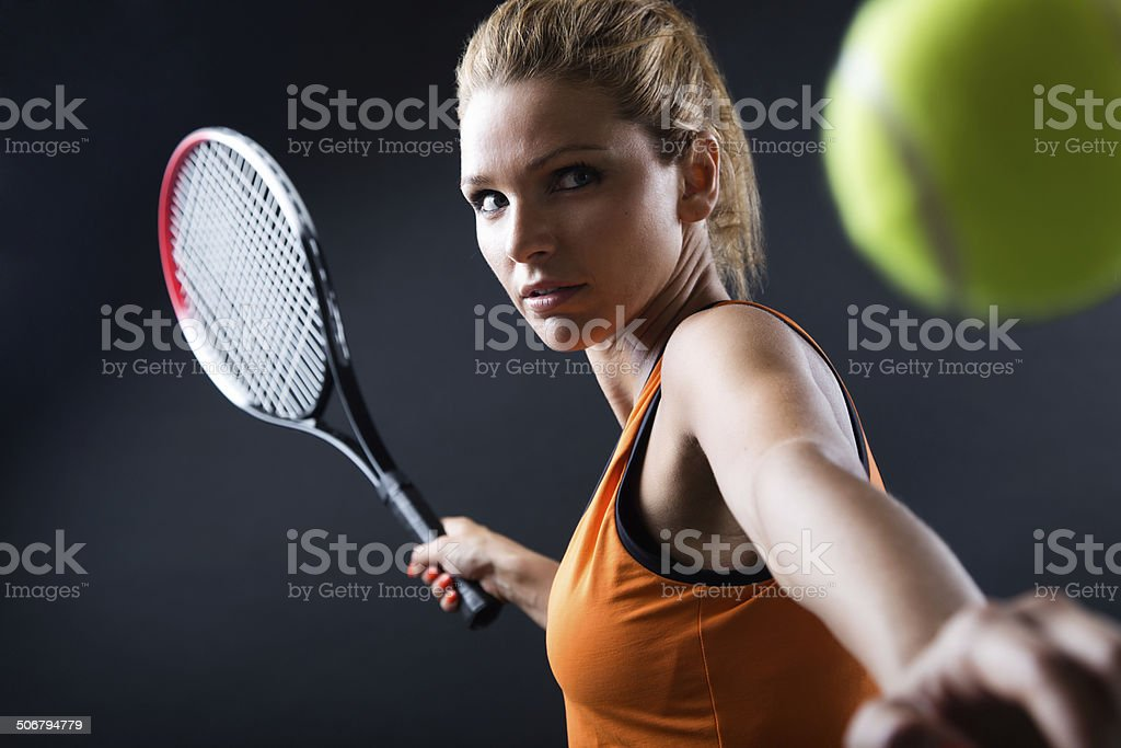 Beautiful woman playing tennis indoor. Isolated on black. stock photo