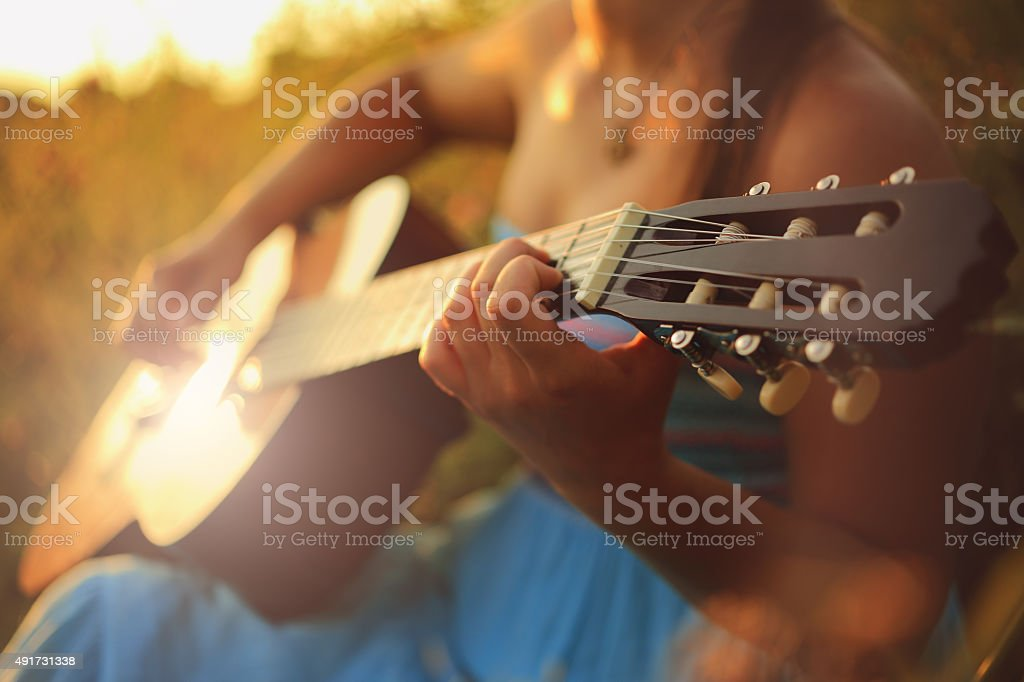 Beautiful woman playing the acoustic guitar in field stock photo