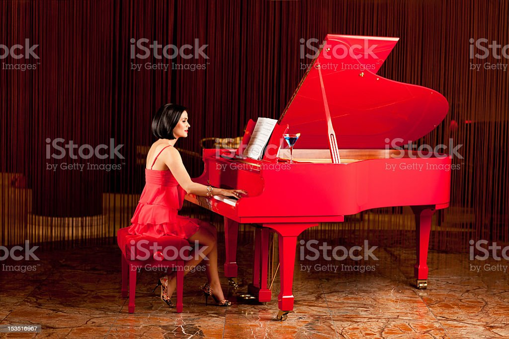 beautiful woman playing the piano stock photo