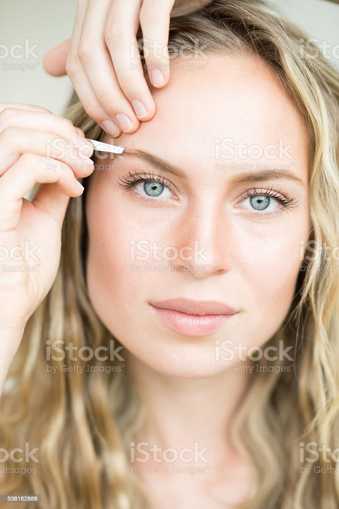 Beautiful Woman plucking her Eyebrows with a Tweezer stock photo