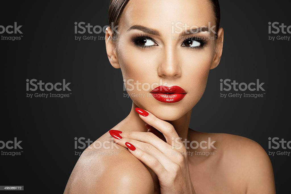 Beautiful woman portrait, beauty on dark background, red nails stock photo