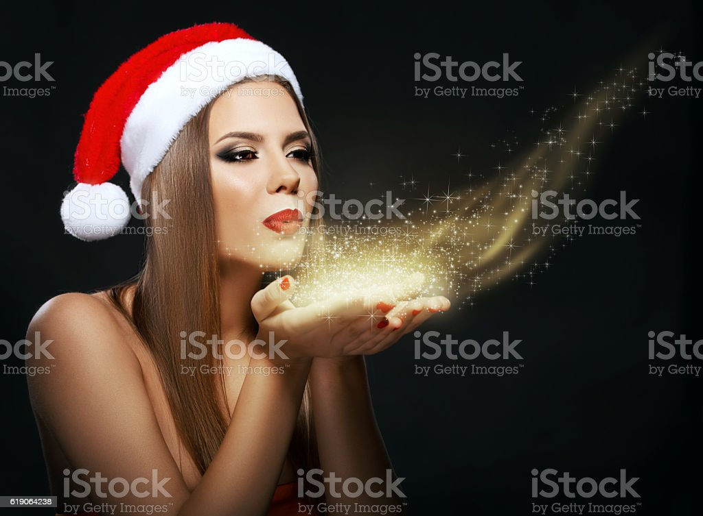 Beautiful woman portrait with Santa's hat, blowing golden dust stock photo