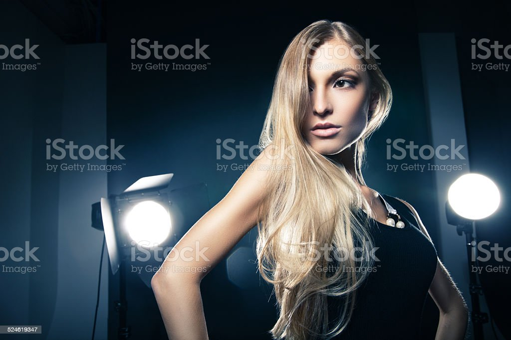 Beautiful woman posing at studio in light flashes stock photo