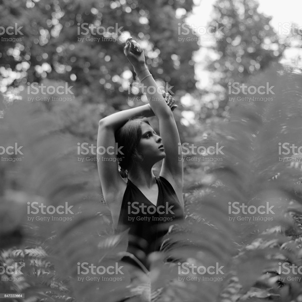 Beautiful woman posing raising hands up among ferns in the stock photo