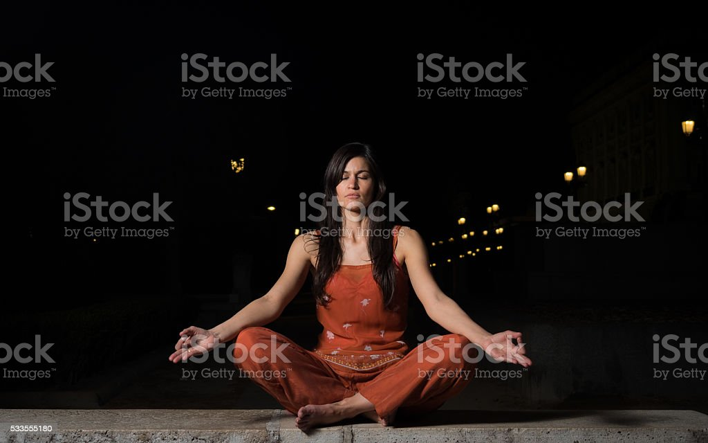 Beautiful woman practicing meditation at night stock photo