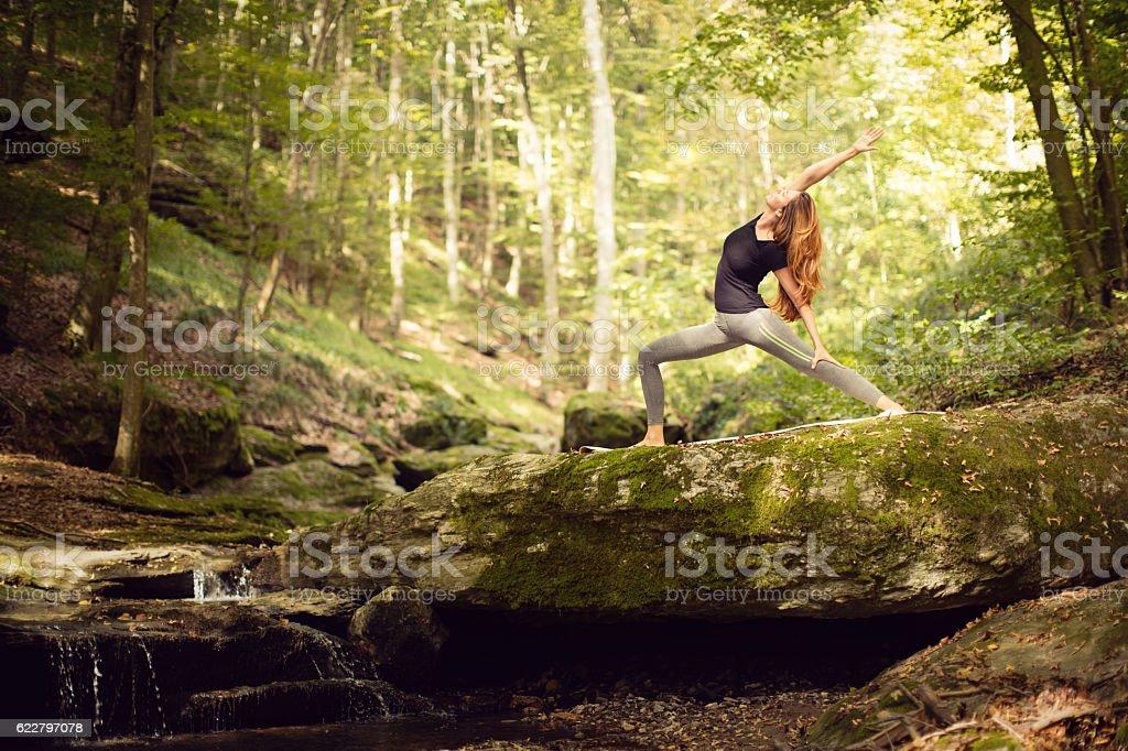 Beautiful woman practicing yoga in nature stock photo