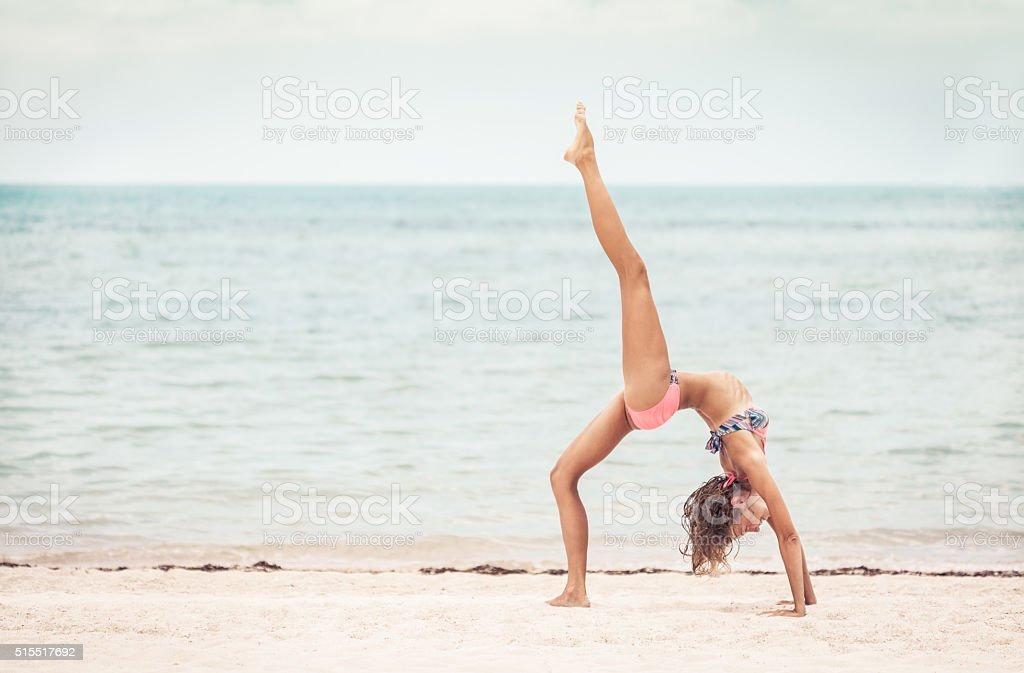 Beautiful woman practising yoga on the shoreline stock photo