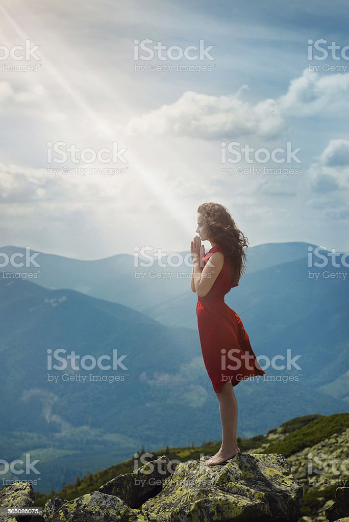 Beautiful woman praying in mountain landscape stock photo