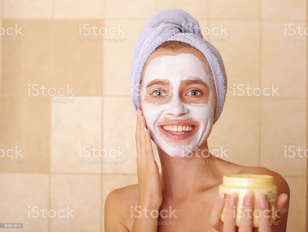 Beautiful woman puts on the face a mask royalty-free stock photo