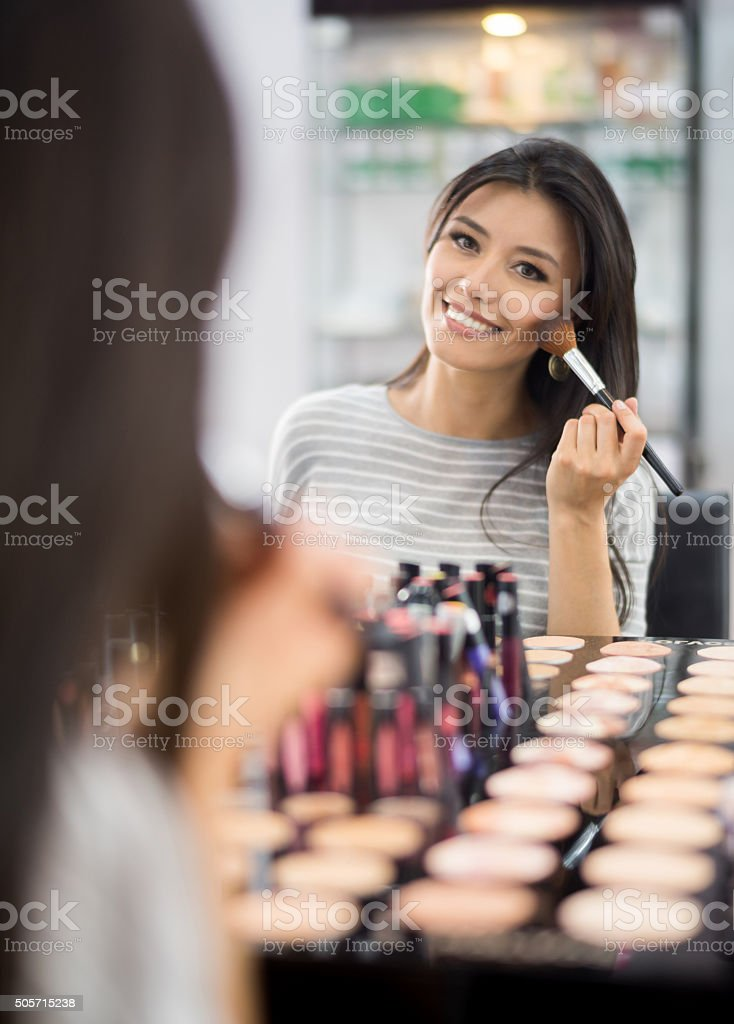 Beautiful woman putting makeup on stock photo