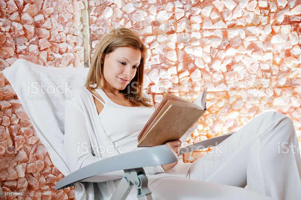 Beautiful woman reading a book in salt room. stock photo