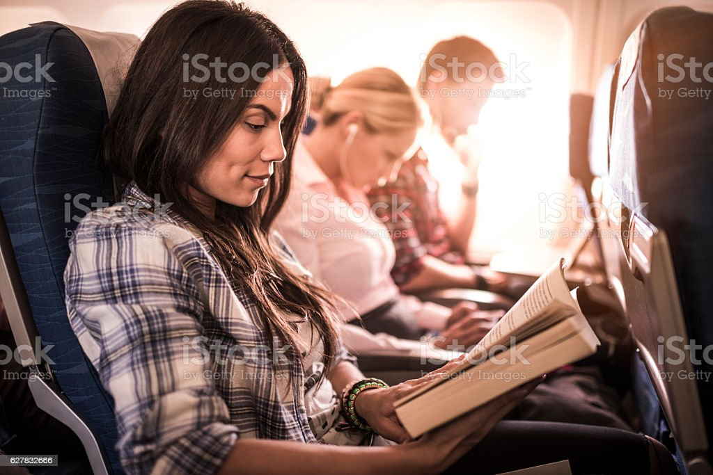 Beautiful woman reading a novel in the airplane. stock photo