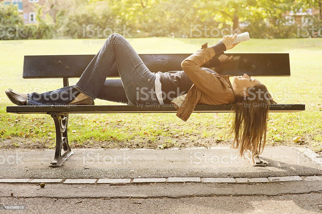 Beautiful Woman Reading and Lying on a Bench royalty-free stock photo