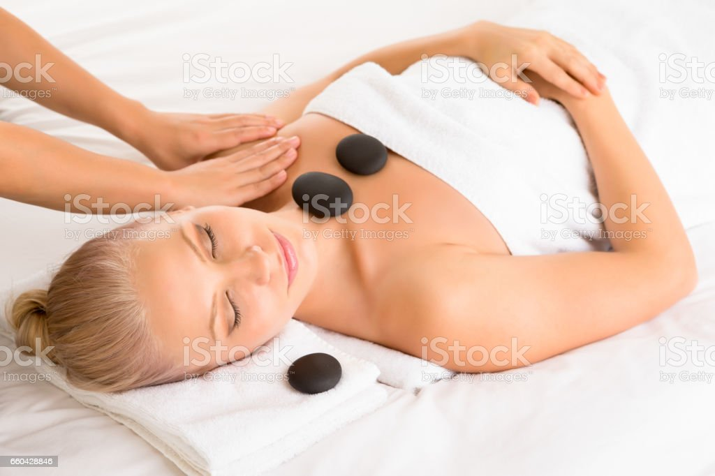 Beautiful woman receiving massage while having hot stone therapy stock photo