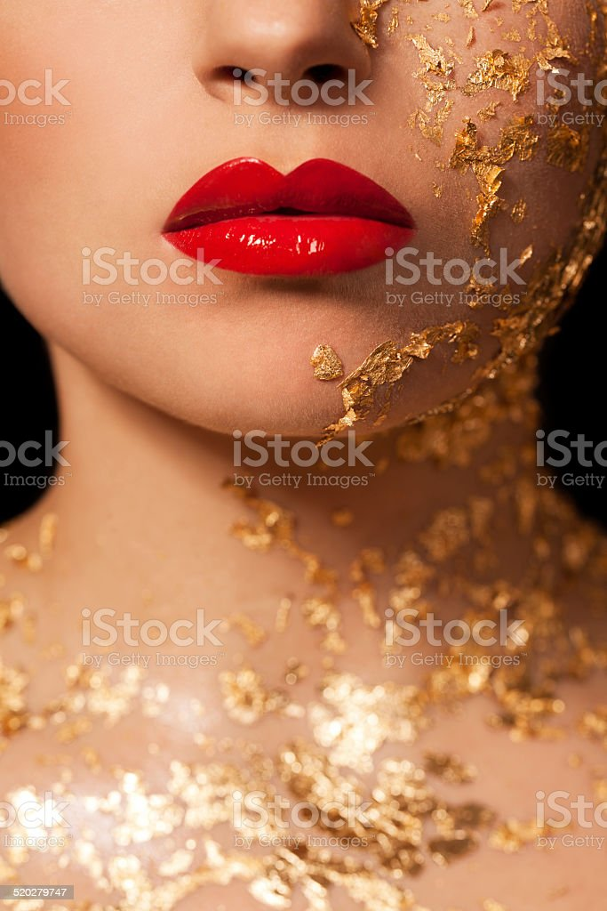 Beautiful woman, creative beauty close up with red lips and gold on...