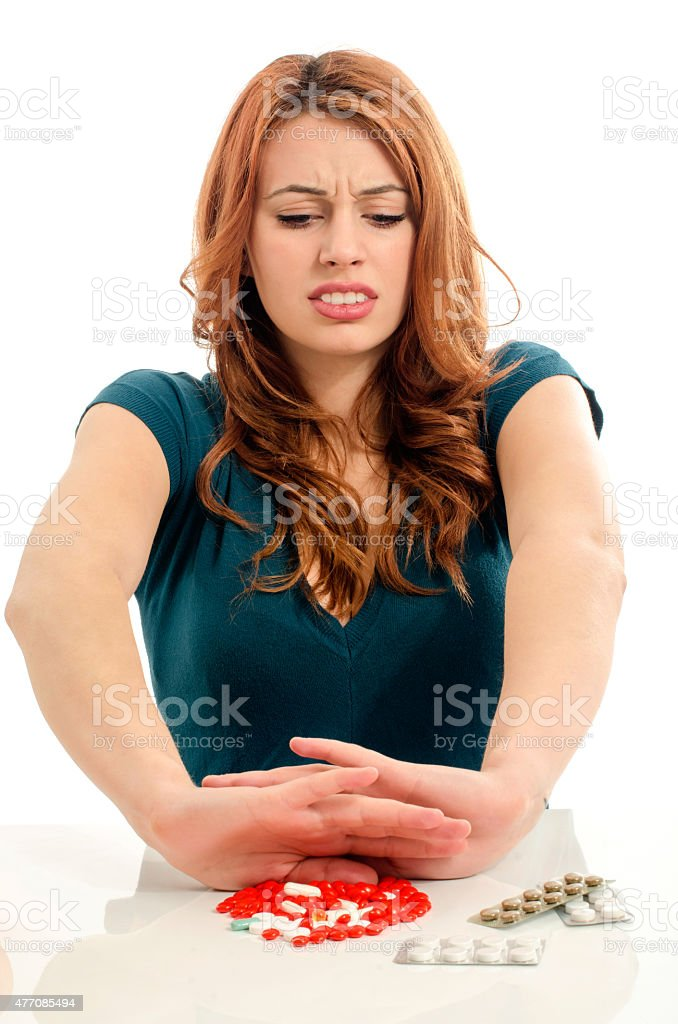 Beautiful woman refusing to take pills. stock photo