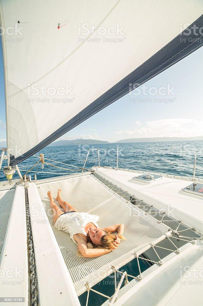 Beautiful woman relaxes on catamaran stock photo