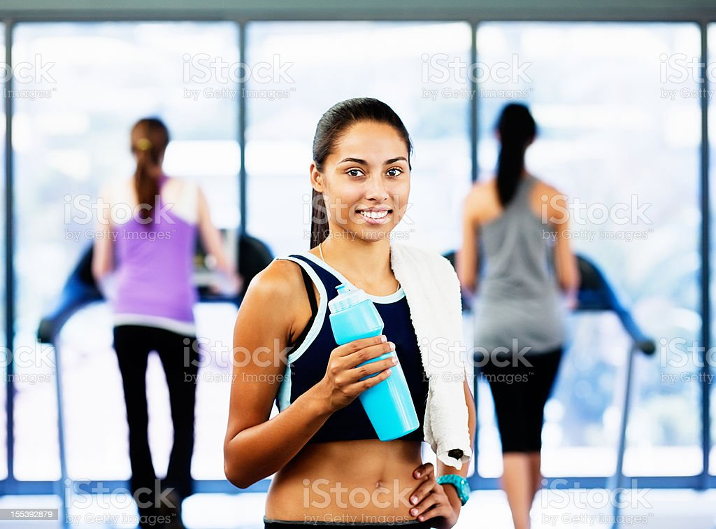 Beautiful woman relaxes smiling in gym stock photo