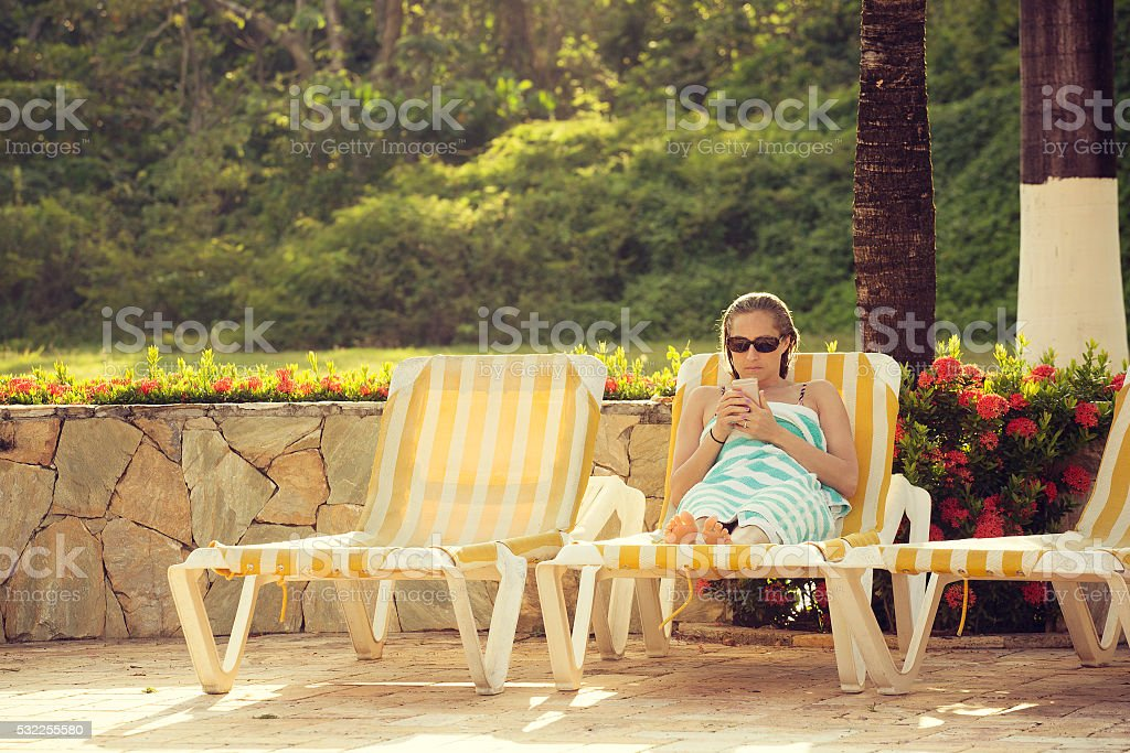Beautiful woman relaxing and checking her cell phone stock photo