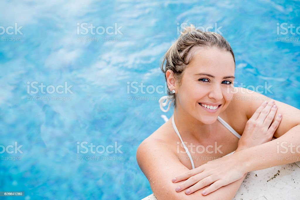 Beautiful woman relaxing at the pool stock photo