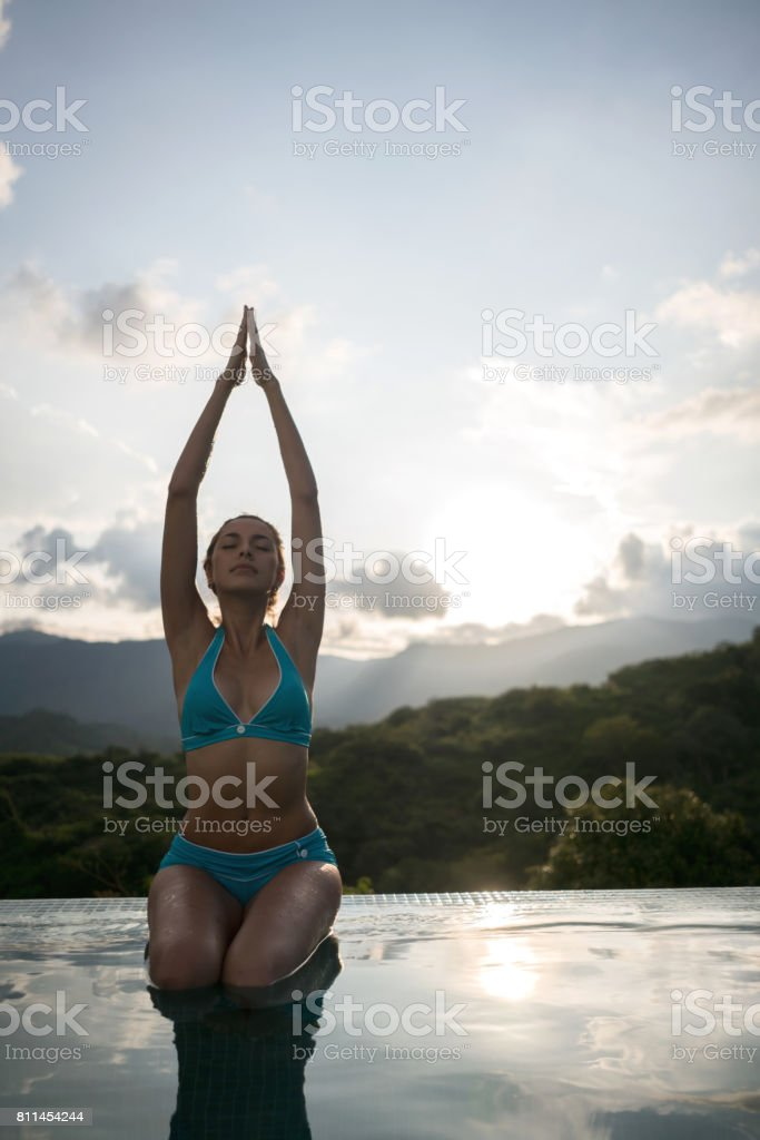 Beautiful woman relaxing by the pool doing yoga exercises stock photo